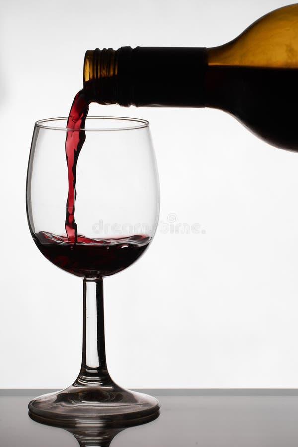 Fermez-vous du versement du vin sec rouge dans un verre de vin en cristal image stock