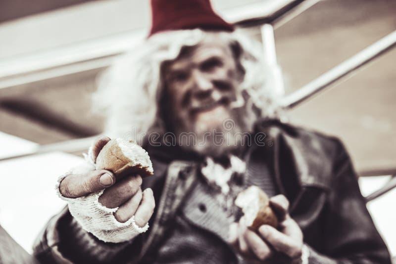 Fermez-vous du vieil almsman dont tenant des morceaux de cuisson et les partageant avec le photographe photo libre de droits