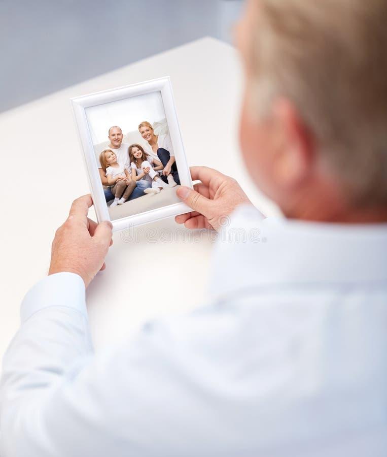 Fermez-vous du vieil homme tenant la photo de famille heureuse images stock