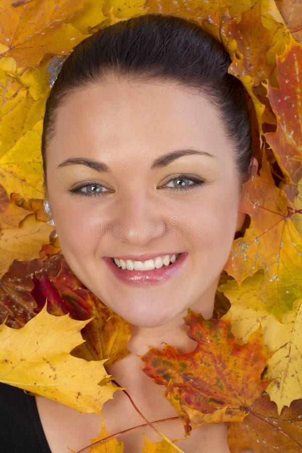Fermez-vous du visage de femme dans des feuilles d'automne photos stock