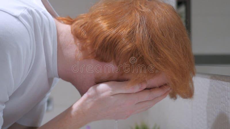 Fermez-vous du visage de lavage de l'homme dans l'évier, salle de bains images stock