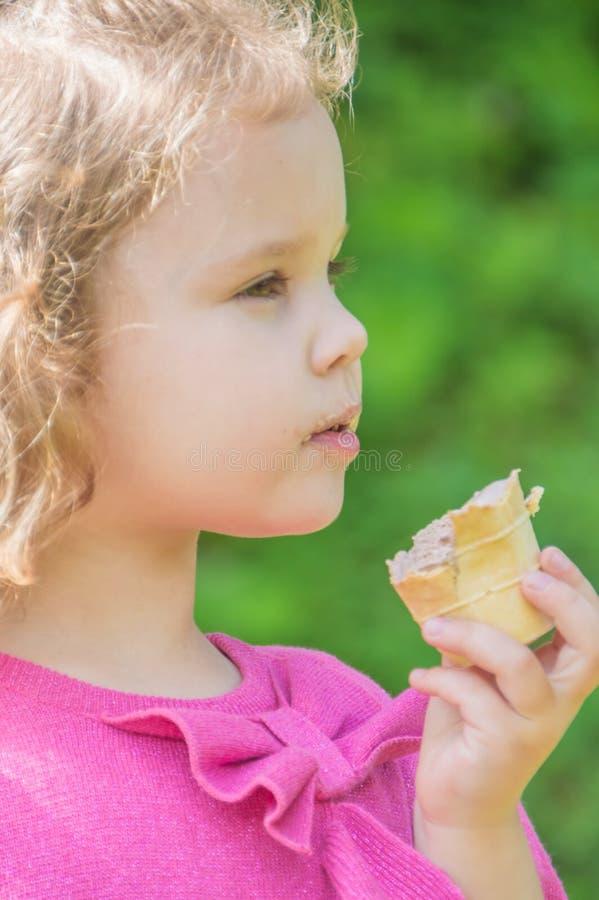 Fermez-vous, enfant avec la crème glacée marche à disposition en parc photos stock