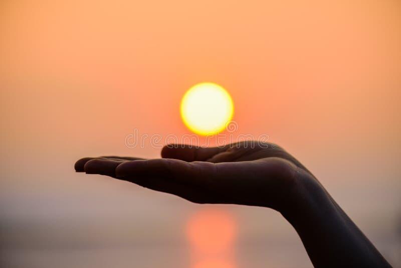 Fermez-vous et silhouette de main tenant le soleil Sun sur la main de femme images libres de droits