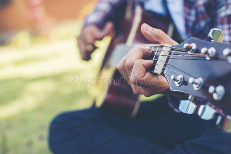 Fermez-vous jeune de la guitare pratiquée de hippie par homme en parc, heureux images libres de droits