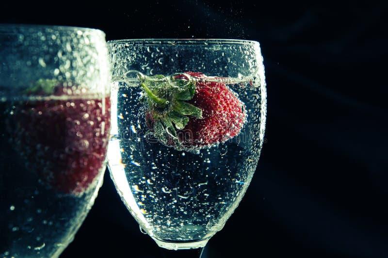 Fermez-vous, macro Fraises rouges juteuses flottant dans une boisson bleue entourée par des bulles Copiez l'espace image stock