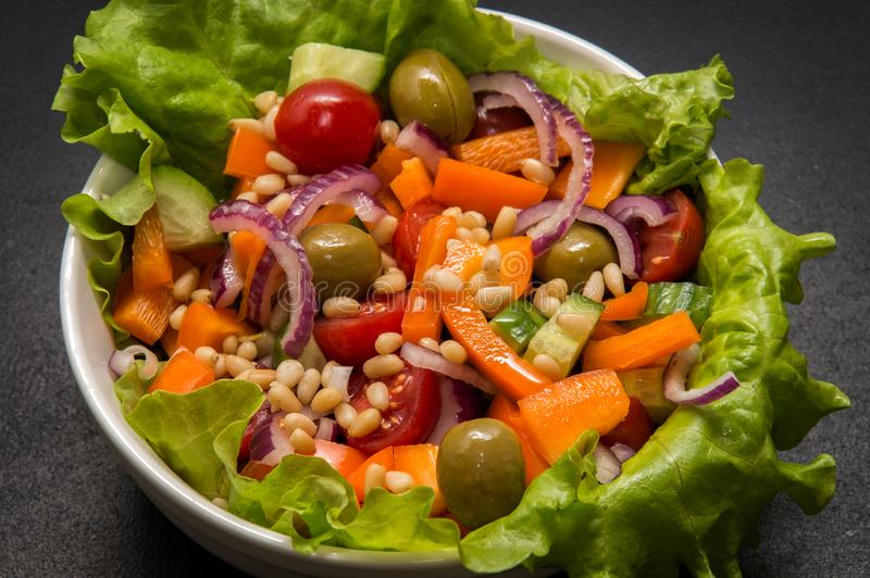 Fermez-vous, macro Nourriture végétarienne Bol de salade végétale avec le tofu et les pignons Fond noir photo libre de droits