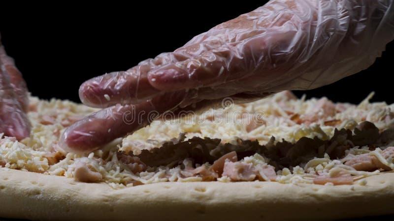 Fermez-vous pour des mains de chef dans les gants transparents touchant la pizza non cuite sur le fond noir, en faisant cuire le  photographie stock libre de droits