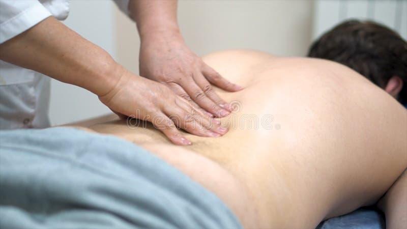 Fermez-vous pour des mains de physiothérapeute faisant de retour le massage au patient menteur, soins de santé, concept de relaxa photographie stock