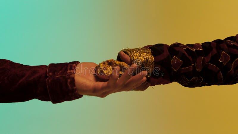 Fermez-vous pour la main orientale d'homme donnant une grande pépite d'or à un autre homme, d'isolement sur le fond vert et jaune photos libres de droits