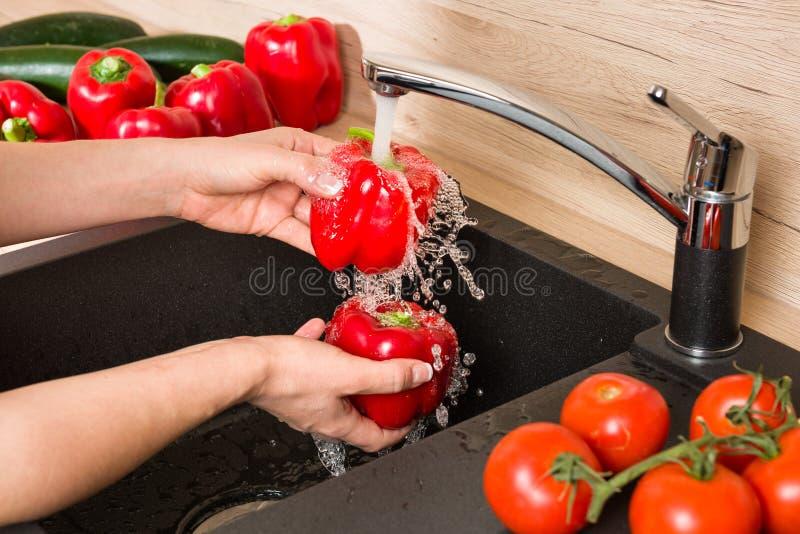 Fermez-vous sur l'évier noir avec des mains lavant des légumes image stock