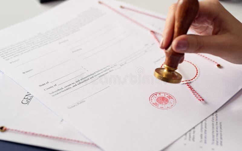 Fermez-vous sur l'encre de main de notaire de la femme emboutissant le document photographie stock