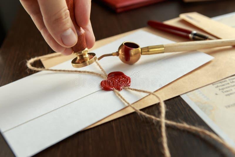 Fermez-vous sur l'encre de main de notaire du ` s de femme emboutissant le document Concept de notaire photographie stock