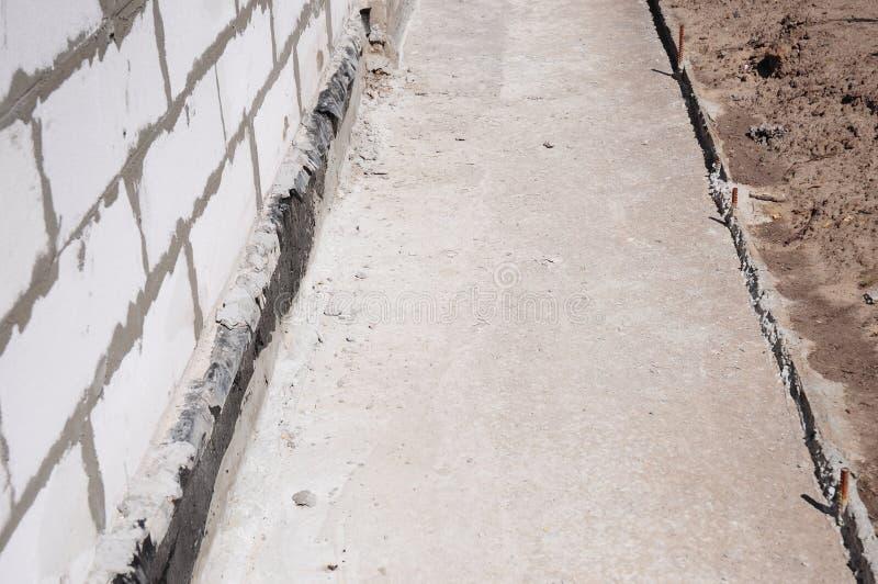 Fermez-vous sur la base de maison imperméabilisant, imperméabilisation humide avec le chemin de contrete pour éviter des fuites d image stock