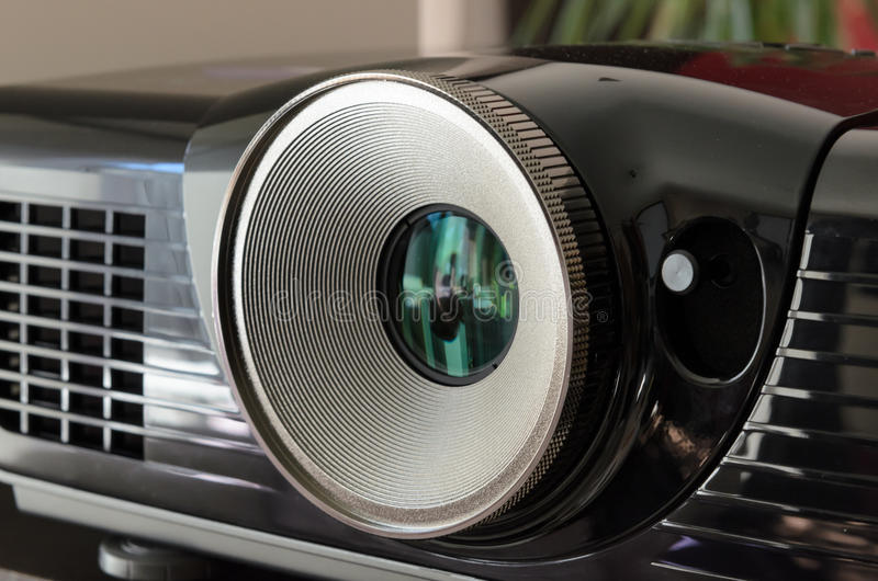 Fermez-vous sur la lentille énorme d'un projecteur à la maison noir de cinéma photo libre de droits