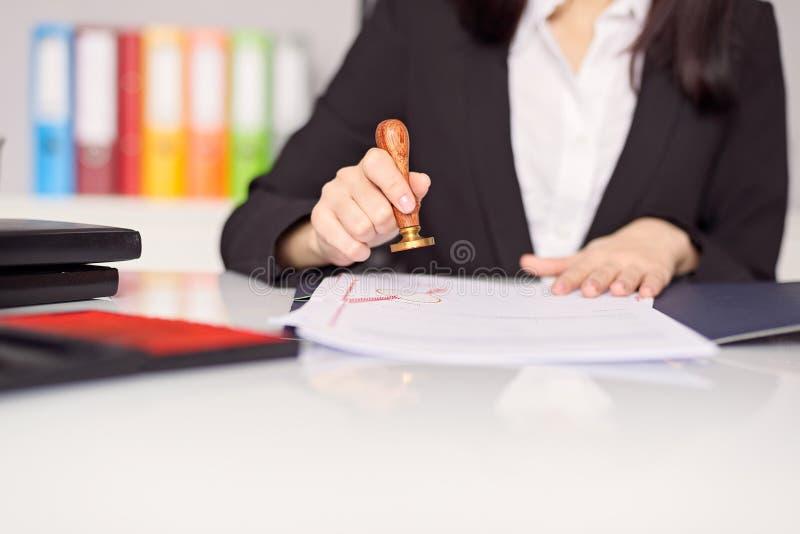 Fermez-vous sur la main de notaire de la femme emboutissant le document photo stock