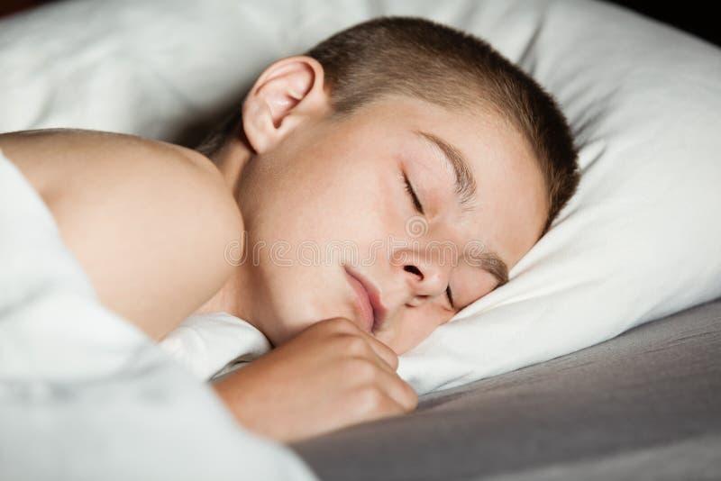 Fermez-vous sur le garçon endormi dans le lit image libre de droits
