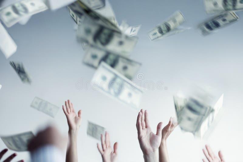 Fermez-vous sur le lancement augmenté par mains et l'argent contagieux dans le ciel photographie stock