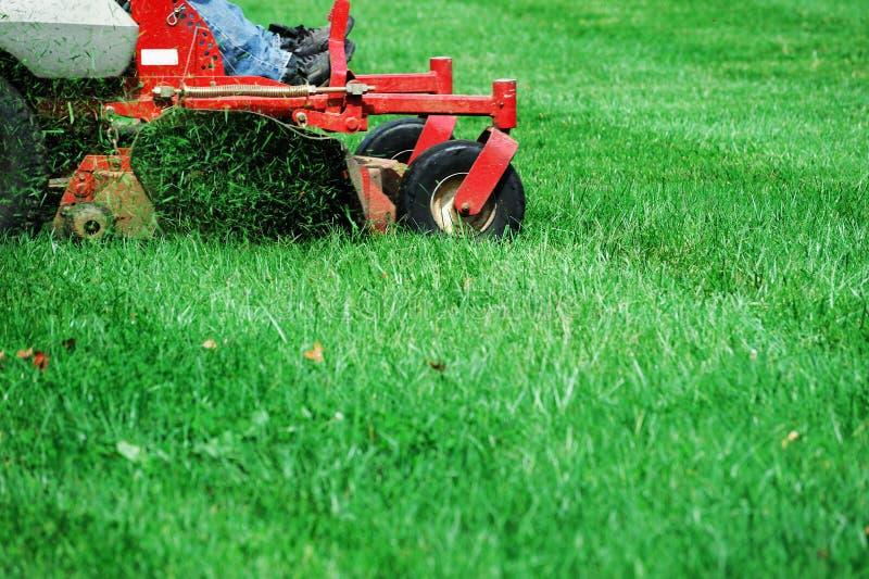 Fermez-vous sur le travailleur fauchant la pelouse images libres de droits