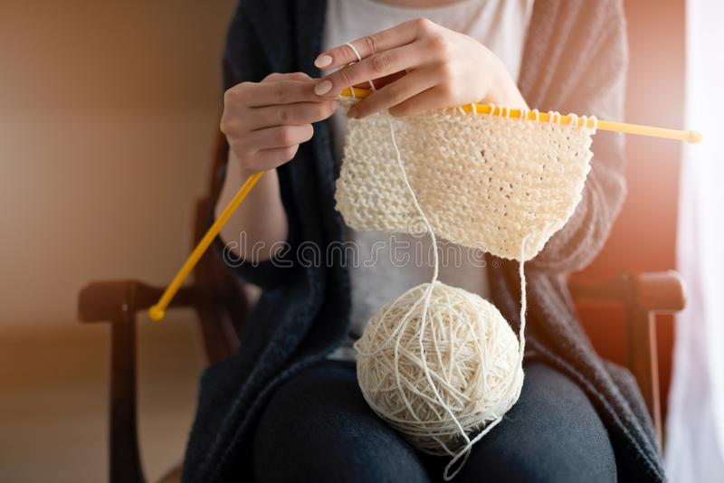 Fermez-vous sur le tricotage des mains de la jeune femme photo libre de droits
