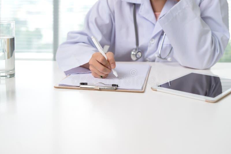 Fermez-vous sur les mains femelles asiatiques de docteur écrivant quelque chose sur le clipb photos libres de droits