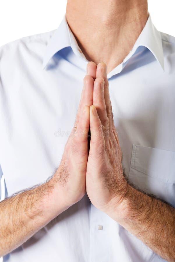 Fermez-vous sur les mains masculines serrées pour prier photos libres de droits