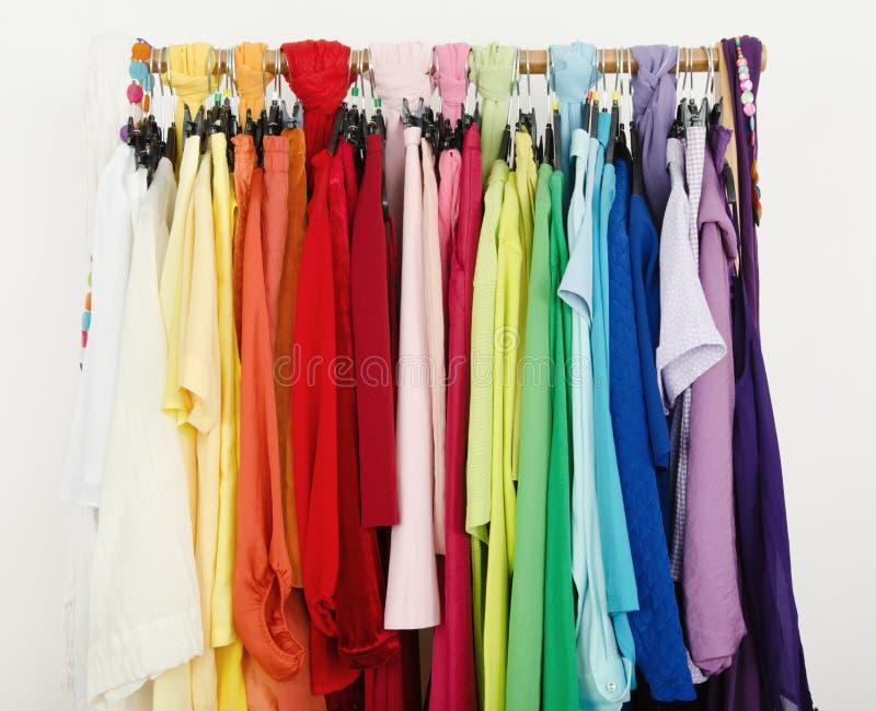Fermez-vous sur les vêtements coordonnés par couleur sur des cintres dans un magasin image stock