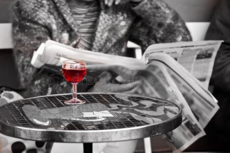 Fermez-vous sur un verre de vin rouge d'une femme dans une barre photos stock