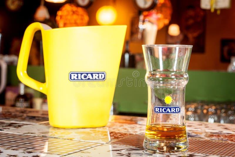 Fermez-vous sur une cruche de Ricard et une bouteille d'eau avec son logo Ricard est des pastis, un anis et apéritif aromatisé pa image stock