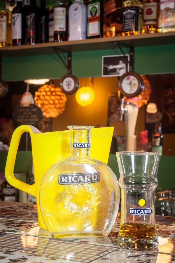 Fermez-vous sur une cruche de Ricard et une bouteille d'eau avec son logo Ricard est des pastis, un anis et apéritif aromatisé pa photos libres de droits
