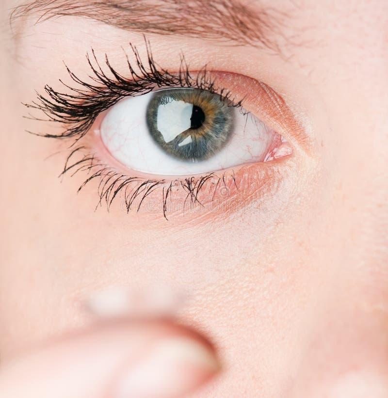 Fermez-vous vers le haut d'insérer un verre de contact dans l'oeil femelle photographie stock