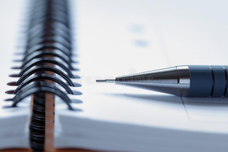 Fermez-vous vers le haut d'un crayon lecteur sur un bloc - notes photos stock