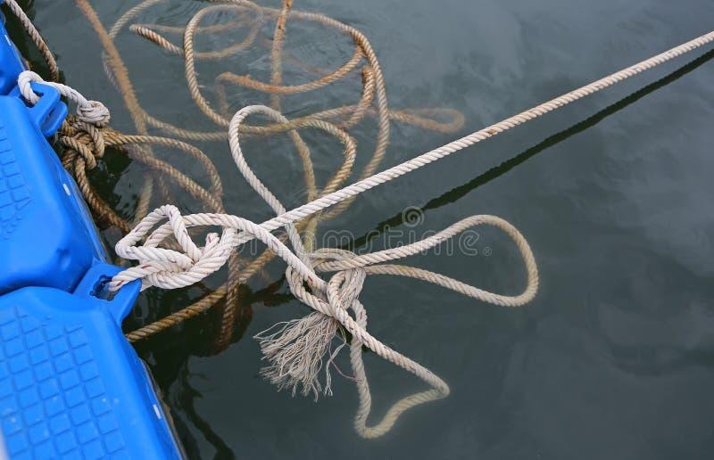Fermez-vous vers le haut d'un noeud de corde de bateau dans une eau image stock