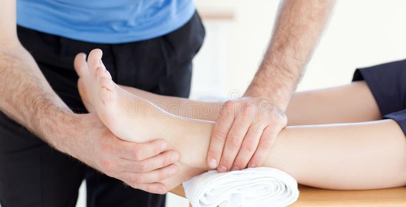 Fermez-vous vers le haut d'un physio- en faisant un massage de pied photos libres de droits