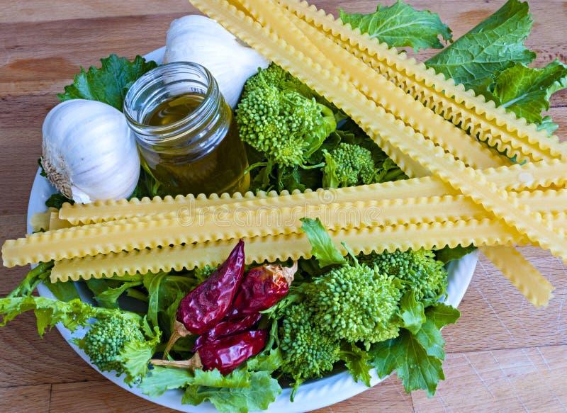Fermez-vous vers le haut de cime di rapa avec le tripoline, l'ail, le poivre de piments et l'huile d'olive supplémentaire de verg images stock