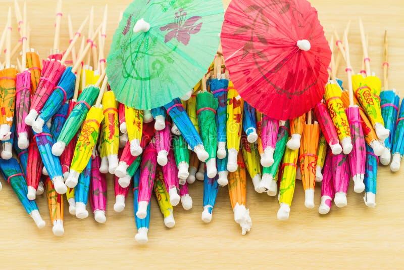 Fermez-vous vers le haut de coloré de beaucoup de parapluies de cocktail sur en bois blanc image stock