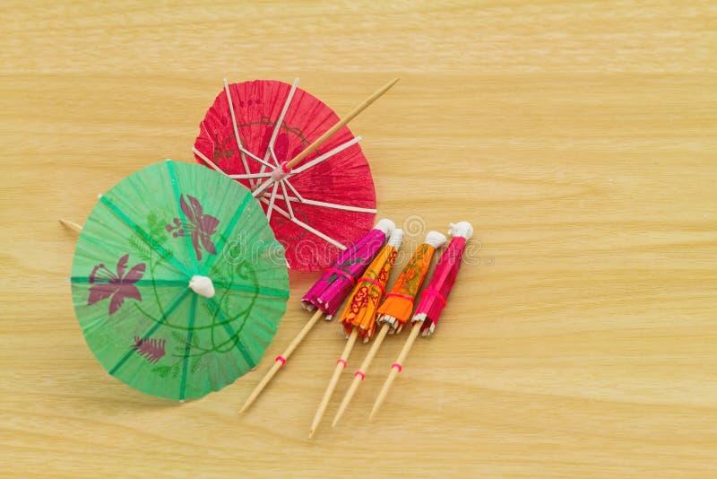 Fermez-vous vers le haut de coloré de beaucoup de parapluies de cocktail sur en bois blanc image libre de droits