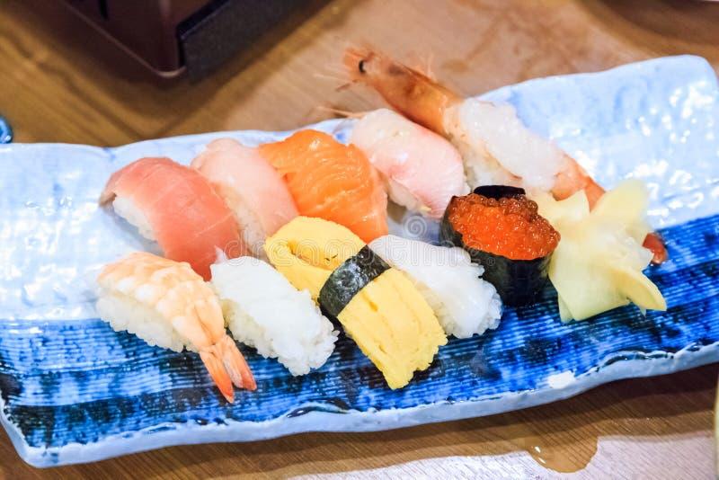 Fermez-vous vers le haut de divers sushi de plat en céramique sur la table en bois photos libres de droits
