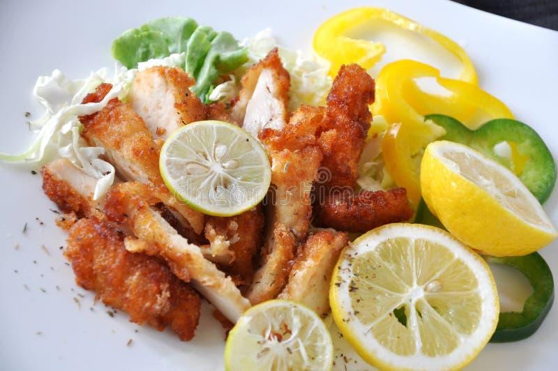 Fermez-vous vers le haut de Fried Chicken avec la chaux et le citron frais images stock
