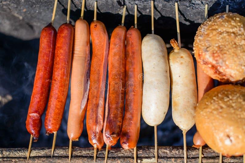 Fermez-vous vers le haut de griller les saucisses et le pain sur des bâtons image stock