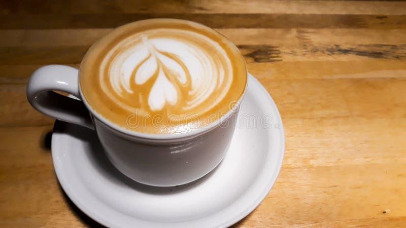 Fermez-vous vers le haut de l'art de latte de tasse de café de tir photo stock