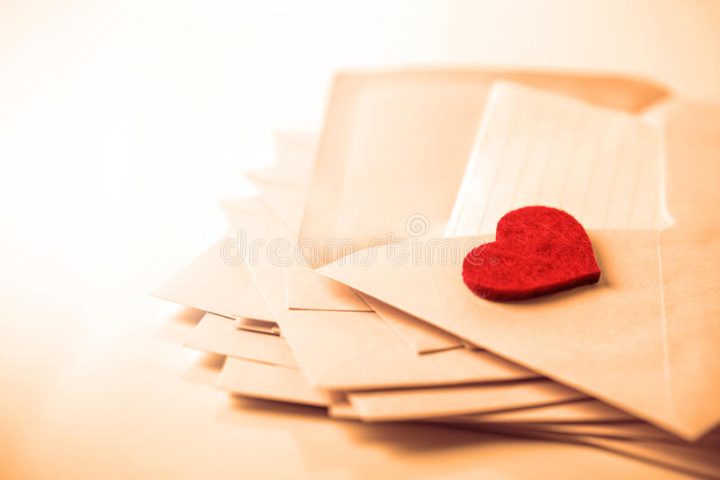 fermez-vous vers le haut de l'empilement des enveloppes roses et d'un papier de lettre de courrier et photo stock