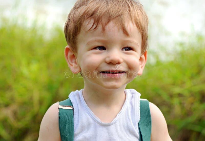 Fermez-vous vers le haut de l'expression de sourire effrontée de visage de bébé garçon de portrait photographie stock