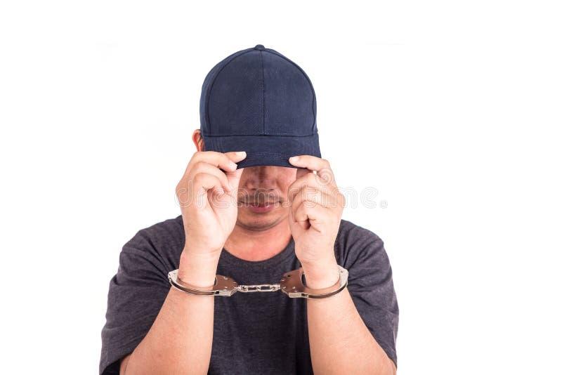 Fermez-vous vers le haut de l'homme avec des menottes sur des mains d'isolement sur le backgroun blanc photographie stock libre de droits