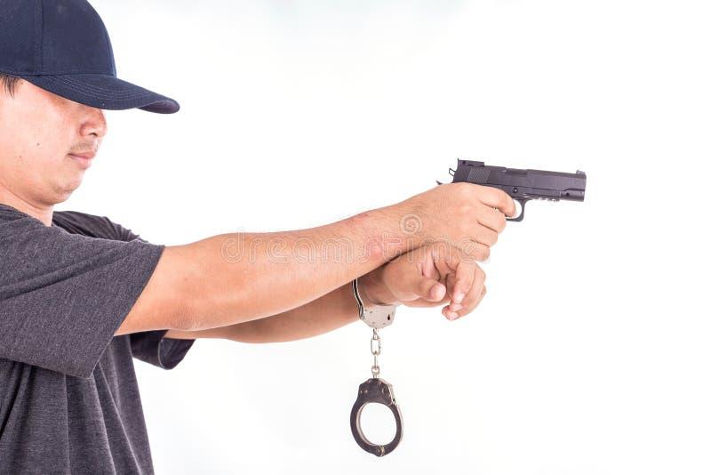 Fermez-vous vers le haut de l'homme avec les menottes et l'arme à feu sur des mains d'isolement sur le blanc photographie stock