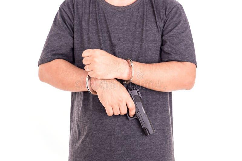 Fermez-vous vers le haut de l'homme avec les menottes et l'arme à feu sur des mains d'isolement sur le blanc images stock
