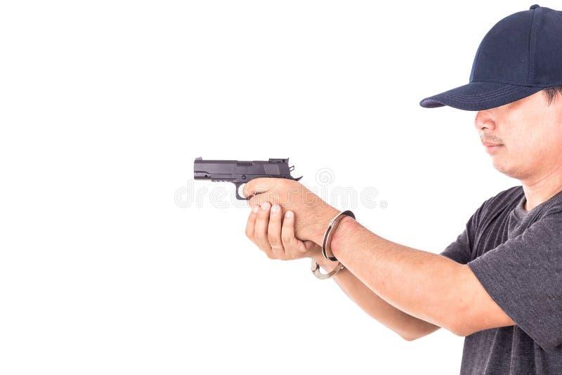 Fermez-vous vers le haut de l'homme avec les menottes et l'arme à feu sur des mains d'isolement sur le blanc photographie stock libre de droits