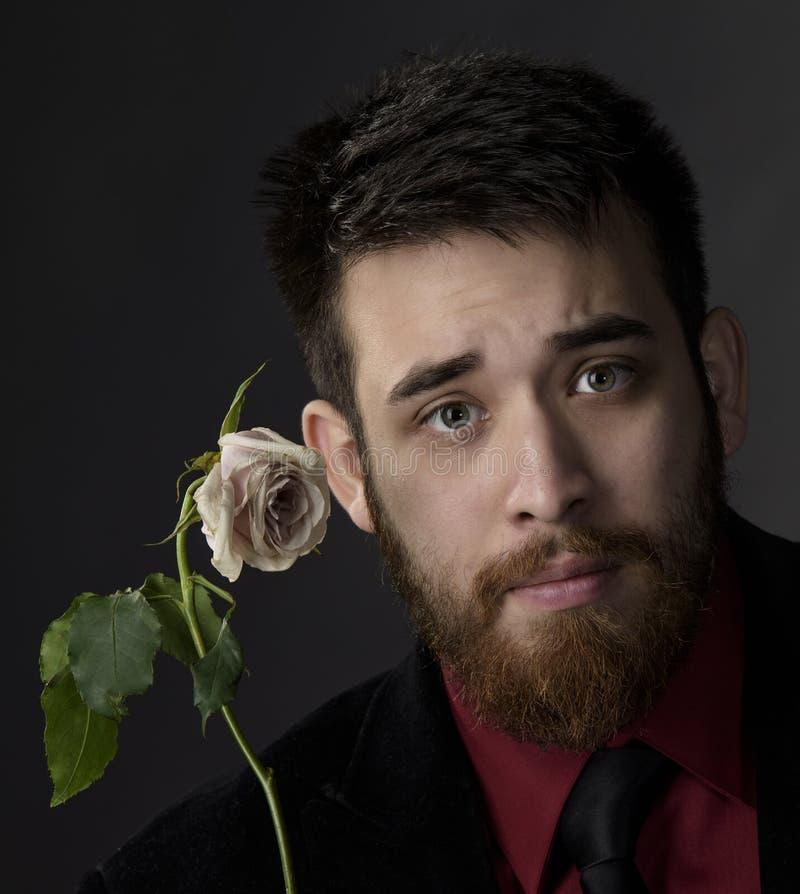 Fermez-vous vers le haut de l'homme bel de barbichette avec Rose blanche images libres de droits