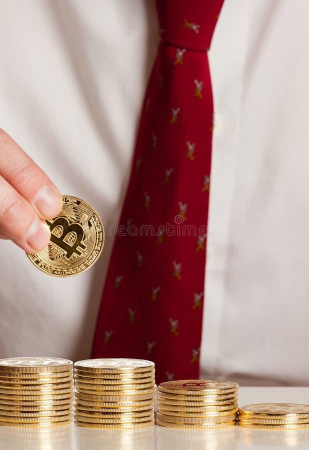 Fermez-vous vers le haut de l'homme d'affaires mettant des bitcoins sur une pile photos stock
