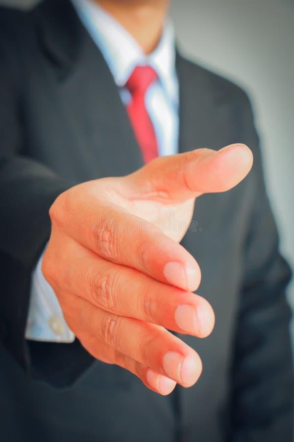Fermez-vous vers le haut de l'homme d'affaires montrant le signe de poignée de main de partner photos stock