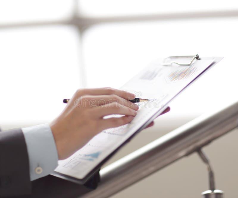 Fermez-vous vers le haut de l'homme d'affaires travaillant avec des données de graphique au bureau photo libre de droits